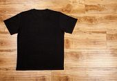 Black plain short sleeved cotton T-Shirt on a planket wooden background poster