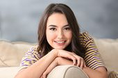 Young beautiful smiling woman resting on sofa at home poster