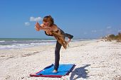 pic of virabhadrasana  - an athletic brown haired woman is doing yoga exercise Virabhadrasana 3 or warrior 3 pose on an empty beach - JPG