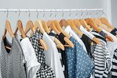 Stylish clothes hanging on wardrobe stand against light background poster