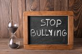Chalkboard with text STOP BULLYING and hourglass on wooden background poster