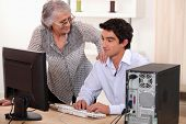 Man  helping elderly woman with computer problems