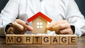 Wooden Blocks With The Word Mortgage And House In The Hands Of A Businessman. The Concept Of Buying  poster