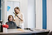 Beauty, Hairstyle Concept, Happy Young Woman And Hairdresser With Hair Iron Making Hairdo At Hair Sa poster