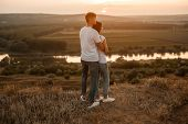 Back View Of Middle Aged Man Hugging Woman While Standing In Countryside During Romantic Date And Ad poster