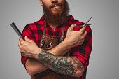 Unrecognizable Bearded Man In Apron Crossing Tattooed Arms With Comb And Scissors While Working In S poster
