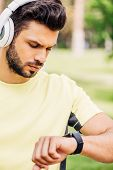 Handsome Bearded Man Looking At Fitness Tracker Outside poster