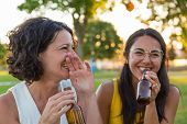 Two Female Friends Drinking Beer And Having Fun In Park. Woman Sitting On Grass, Holding Bottles, Ch poster