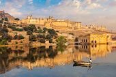 Famous tourist destination Amer (Amber) fort and Maota lake with man in boat in the morning. Jaipur, poster