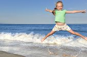 Child Girl Jumping On Summer Beach. Cheerful Little Girl Jumping And Hovering In The Air On The Back poster