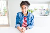 Beautiful young african american woman with afro hair wearing casual denim jacket smiling looking si poster