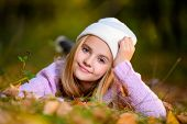 A pretty young girl is on the ground with golden leaves. Autumn fashion, beauty. poster