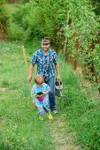 Growing Plants. Boy And Father In Nature With Watering Can And Shovel. Dad Teaching Son Care Plants. poster