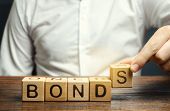 Businessman Puts Wooden Blocks With The Word Bonds. A Bond Is A Security That Indicates That The Inv poster