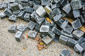 Pile Of Black Natural Stone Cubes For Making Outdoor Pavement Tiles. Chaotic Stack Of Broken Road Ti poster