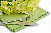 Smple Informal Place Setting With Green Napkin, Hydrangea Flowers And Stainless Steel Cutlery On Whi poster