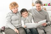 Loving Grandparents With Grandchild Sitting On Sofa poster