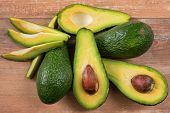 Close-up Photo Of Fresh Sliced Avocados, Brown Seeds Visible On Brown Wooden Background. Vegetarian  poster