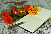 Nasturtium Flowers In Glass Bottle And Open Diary With Pencil On Wooden Table. Esoteric, Occult And  poster