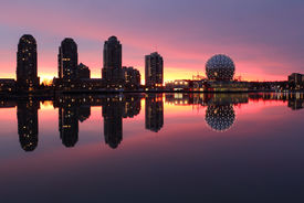 stock photo of geodesic  - Sunrise lights up the Vancouver skyline on the edge of False Creek including condominium towers and the geodesic dome of Science World - JPG