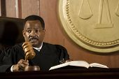 African American judge holding mallet in courtroom