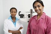 Female doctor standing beside patient on weighing machine