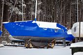 stock photo of tarp  - Bright blue tarp covering a sailboat in winter - JPG