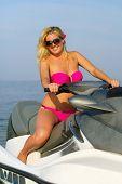 image of jet-ski  - Cute smiling young blonde on a jet ski - JPG