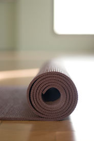 image of yoga mat  - Simple close up of a yoga mat rolled up in a yoga studio - JPG
