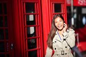 stock photo of phone-booth  - London woman taking on smart phone by red phone booth - JPG