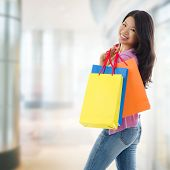 Happy Asian shopping woman smiling holding many shopping bags at the mall. Casual Asian shopper girl