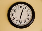 stock photo of arrow  - Close up of Big brown clock on yellow wall - JPG
