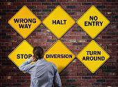 Businessman going the wrong way in front of a brick wall with stop, wrong way, halt, no entry, diver