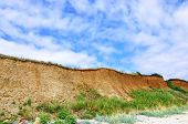 stock photo of geologie  - Earthen near to the sea with the blue sky with clouds - JPG