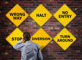 picture of no entry  - Businessman going the wrong way in front of a brick wall with stop - JPG