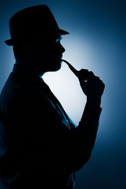 picture of thinkers pose  - Silhouette of a man wearing a hat and smoking pipe - JPG