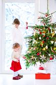 pic of girl next door  - Happy children playing next to a Christmas tree - JPG