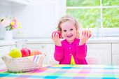 picture of day care center  - Funny happy laughing child adorable toddler girl with curly hair wearing a pink shirt eating red and green apples for healthy snack sitting in a white sunny kitchen with window at home or day care center - JPG