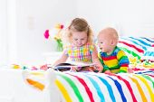 image of boys  - Two children cute curly little toddler girl and a funny baby boy brother and sister reading a book sitting in a sunny bedroom on a wooden white bed with colorful rainbow bedding enjoying a nice weekend morning - JPG