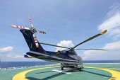 stock photo of helicopter  - helicopter parking landing on offshore platform. Helicopter transfer crews or passenger to work in offshore oil and gas industry.