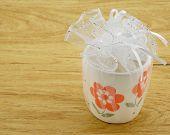 stock photo of keepsake  - Ceramic flower taken as souvenirs wrapped with white gauze tied with a white ribbon - JPG