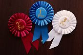 image of rosettes  - Three winners rosettes for first second and third place in pleated blue red and white ribbon respectively with central text - JPG