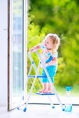 stock photo of girl next door  - Cute laughing curly toddler girl washing a big window with a squeegee in beautiful white living room with door into the garden standing on a ladder next to a blue bucket with water detergent solution spray bottle and sponge - JPG