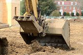 image of track-hoe  - Small track hoe excavator to digging a water line trench on a new commercial residential development