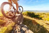 stock photo of exercise bike  - Mountain biker in action on rocks looking at downhill trail against blue sky concept for healthy lifestyle - JPG