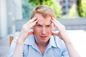 picture of pain-tree  - Closeup portrait stressed young business man in blue shirt hands on head with bad headache isolated background of trees outside - JPG
