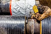 pic of pipe-welding  - Welder is welding a pipe in a trench - JPG