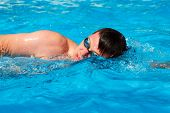 foto of watersports  - Man swimmer swimming crawl in blue water - JPG