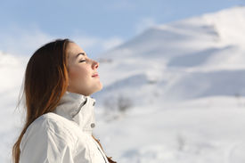 image of breathing exercise  - Profile of an explorer woman breathing fresh air in winter with a snowy mountain in the background - JPG