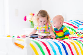 picture of little sister  - Two children cute curly little toddler girl and a funny baby boy brother and sister reading a book sitting in a sunny bedroom on a wooden white bed with colorful rainbow bedding enjoying a nice weekend morning - JPG